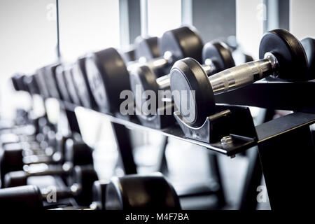 Rows of dumbbells on a rack in the gym. - Stock Photo