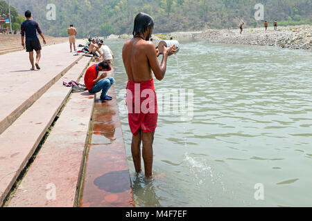 RISHIKESH, INDIA - APRIL 17, 2017: A Hindu sadhu taking a bath at the holy river Ganges in Rishikesh on the 17th - Stock Photo