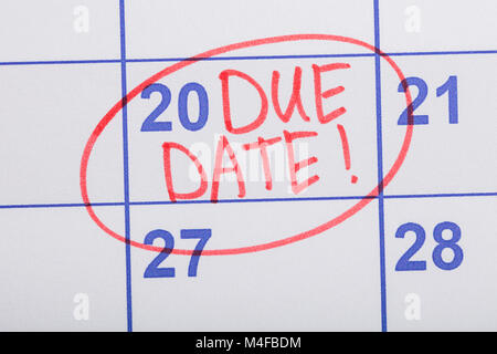 Close-up Of Red Circle Marked With Words Due Date Written On A Calendar - Stock Photo