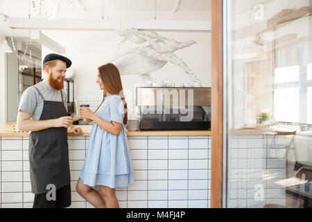 Coffee Business Concept - young smart bearded bartender enjoy talking and giving take away cup of coffee to pretty - Stock Photo