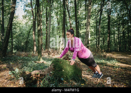 Full length portrait of a female jogger warming up on her own and getting ready for a jog. - Stock Photo