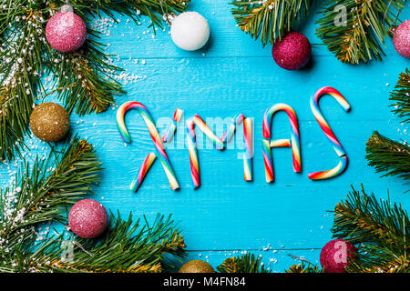 Photo of blue table with spruce branches, colorful balls and caramel stick inscriptions - Stock Photo