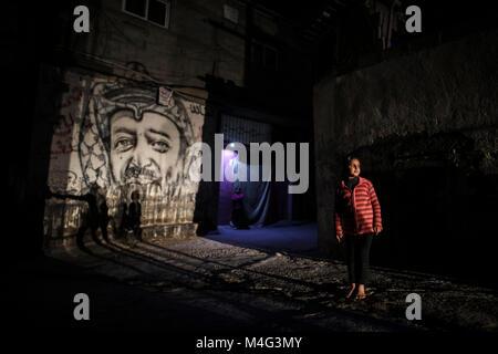Gaza City, Palestinian Territories. 15th Feb, 2018. Palestinian girl stands next to a graffiti of late Palestinian - Stock Photo