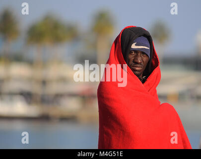 Malaga, Malaga, Spain. 16th Feb, 2018. A migrant is seen covered by red blanket. Arrival of a group of migrants - Stock Photo