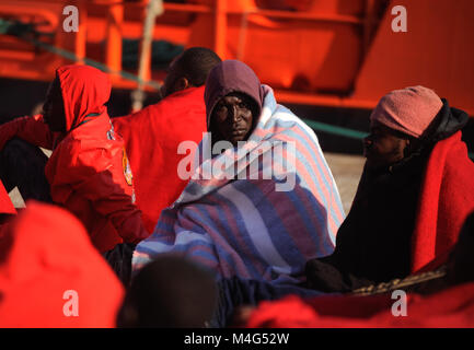 Malaga, Malaga, Spain. 16th Feb, 2018. A migrant looks on as he rests on the ground. Arrival of a group of migrants - Stock Photo