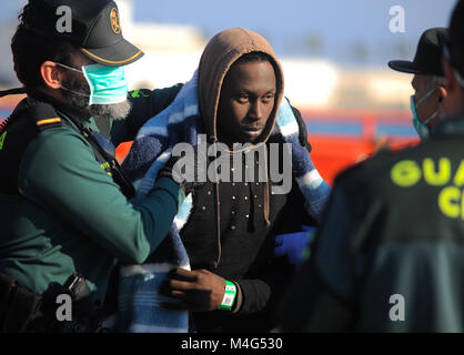 Malaga, Malaga, Spain. 16th Feb, 2018. A migrant is being led by member of Civil Guard. Arrival of a group of migrants - Stock Photo