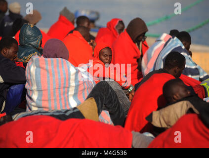 Malaga, Malaga, Spain. 16th Feb, 2018. A group of migrants are seen resting on the ground. Arrival of a group of - Stock Photo