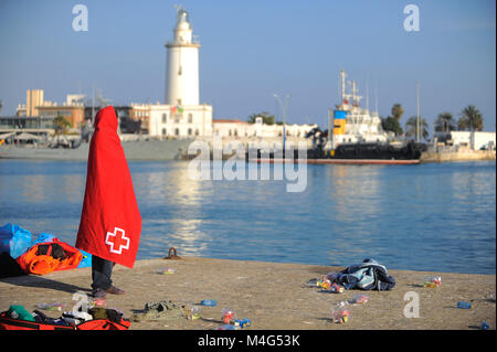 Malaga, Malaga, Spain. 16th Feb, 2018. A migrant stands covered by red blanket. Arrival of a group of migrants rescued - Stock Photo