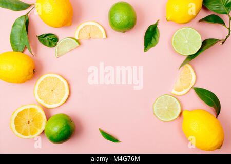 Flat lay of citrus fruits like lime and lemon with lemon tree leaves on light pink background making a frame - Stock Photo