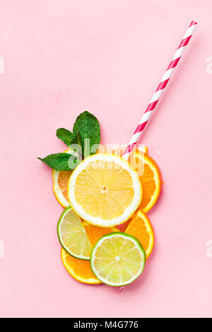 Glass of juice made of citrus slices with mint leaves and a straw on light pink background. Citrus juice concept - Stock Photo