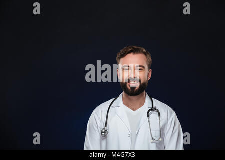 Portrait of a happy male doctor dressed in uniform with stethoscope standing and looking at camera isolated over - Stock Photo