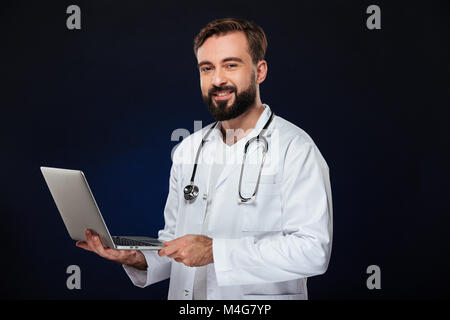 Portrait of a happy male doctor dressed in uniform with stethoscope holding laptop computer isolated over dark background - Stock Photo