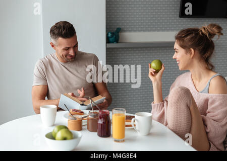 Portrait of a young loving couple having breakfast while sitting at the table in a kitchen at home, man is reading - Stock Photo