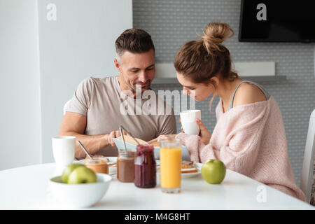 Portrait of a smiling loving couple having breakfast while sitting at the table in a kitchen at home, man is reading - Stock Photo