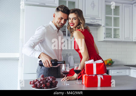 Happy woman with bright make up smiling to camera while her handsome man pouring wine into glasses at home on celebration - Stock Photo