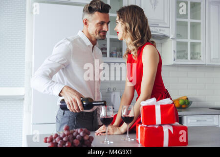 Young man in white shirt pouring wine into glasses and looking at his gorgeous woman in red dress on valentines - Stock Photo