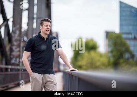 Portrait of a man posing on a city bridge. Medium shot. - Stock Photo