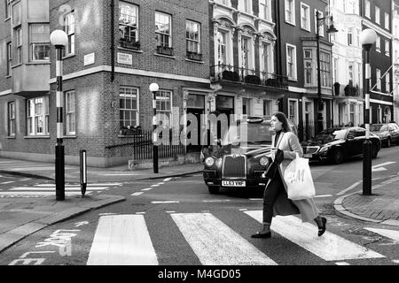 Black & White Photograph of a woman on a zebra crossing, London, England, UK. Credit: London Snapper - Stock Photo