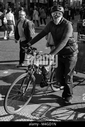 Black & White Photograph of a Cyclist wearing flying goggles, Whitehall, London, England, UK. Credit: London Snapper - Stock Photo