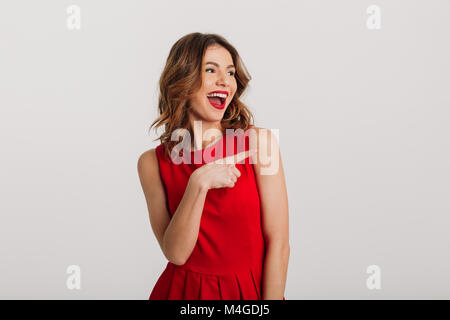 Portrait of a joyful young woman dressed in red dress pointing finger away at copy space isolated over white background - Stock Photo