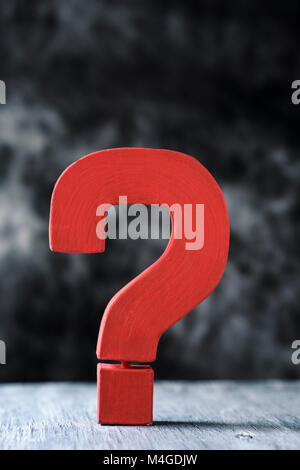 a red three-dimensional question mark on a gray rustic wooden surface against a dark background, with some blank - Stock Photo