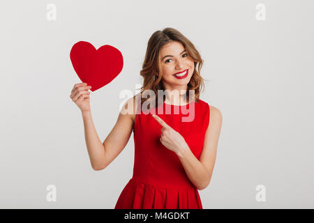 Portrait of an attractive young woman dressed in red dress pointing finger at paper heart isolated over white background - Stock Photo