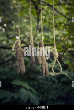 noose and hanged dolls in wood - Stock Photo