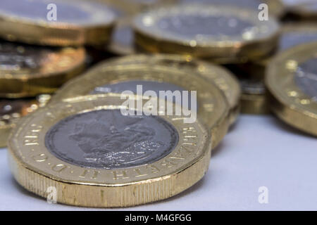 British one pound coins in a pile symbolised by £1 - Stock Photo