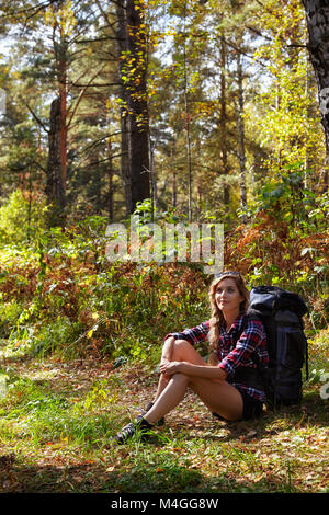 Young blonde female tourist with a backpack sitting on the sidelines of the forest path. Russia, Siberia, Salair - Stock Photo