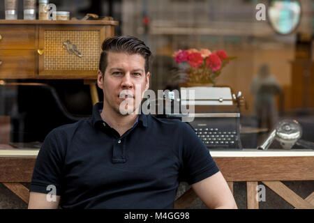 Portrait of a man seated in front of an antiques store. Close up. - Stock Photo