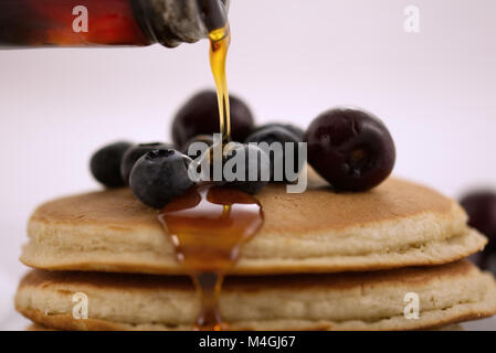Breakfast pancakes with blueberries, cherries and maple syrup isolated on a white background with very shallow depth - Stock Photo