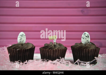 Easter time chocolate cupcakes with egg decorations on top and Easter text or words - Stock Photo