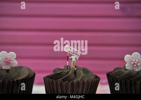 Easter time chocolate cupcakes with flower decorations on top and Easter text or words - Stock Photo