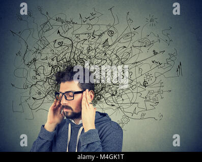 Thoughtful stressed young man with a mess in his head - Stock Photo