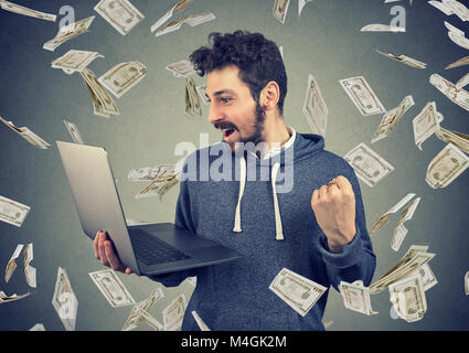 Successful young man using laptop building online business making money dollar bills cash falling down. Money rain. - Stock Photo