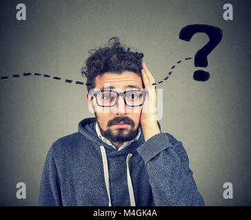 Young hipster man having question in mind and looking puzzled at camera. - Stock Photo