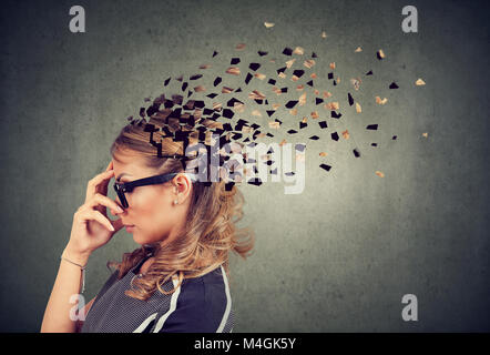 Memory loss due to dementia or brain damage. Side profile of a woman losing parts of head as symbol of decreased - Stock Photo