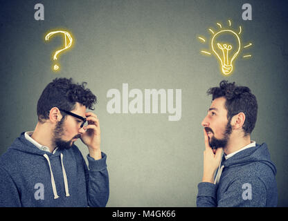 Two men thinking one has a question another solution with light bulb above head isolated on gray background. - Stock Photo