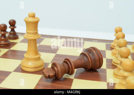King at the queen's feet on the chessboard - Stock Photo