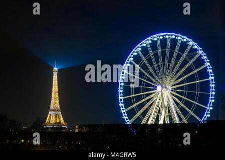PARIS, FRANCE - CIRCA DECEMBER 2016: The Eiffel Tower and the Roue De Paris (Paris ferris wheel) at night. - Stock Photo