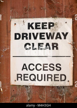 keep driveway clear no parking white and black sign board - Stock Photo