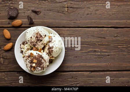 Tasty chocolate ice cream with nuts in bowl on wooden background with copy space. Top view, flat lay - Stock Photo