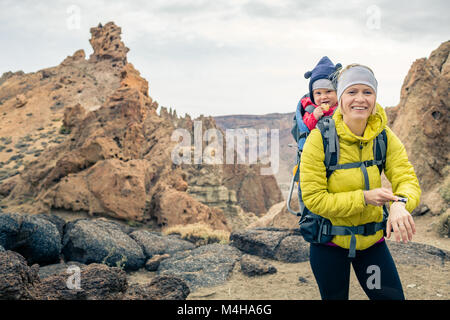 Super mother with baby boy travelling in backpack. Hiking adventure with child on autumn family trip in mountains. - Stock Photo