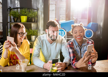 Friends sitting with phone in the cafe - Stock Photo