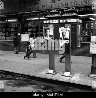 Passers-by walk past electoral posters on phone booths in Chinatown, New York City. - Stock Photo