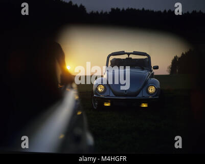 A VW Beetle Convertible with open top on a field at sunset seen in the rear view mirror of a Golf Convertible. - Stock Photo