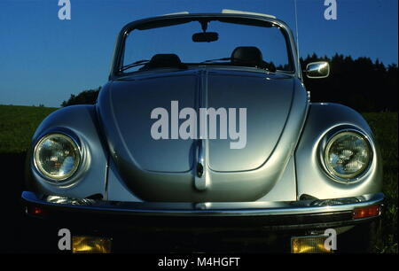A VW Beetle Convertible with open top on a field. - Stock Photo