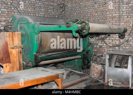 Old dysfunctional vintage machinery used for the production of textiles - Stock Photo