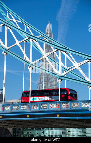 Red London bus crossing Tower Bridge with the Shard in the background, London, England, UK - Stock Photo