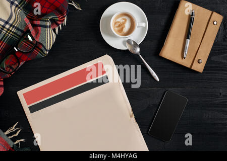 Smart phone with black display on wooden background. Newspaper and coffee on wooden table. Top view. Copy space. - Stock Photo